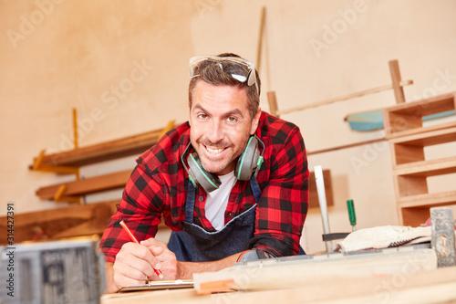 Junger Handwerker mit Bleistift und Checkliste #314427391
