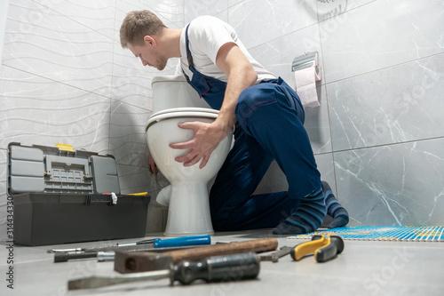 man plumber in uniform installing toilet bowl using instrument kit professional Tapéta, Fotótapéta