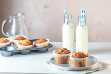 Vanilla Caramel Muffins In Paper Cups And Bottles Of Milk On White Wooden Background. Delicious Cupcake. Homemade Biscuit Cakes