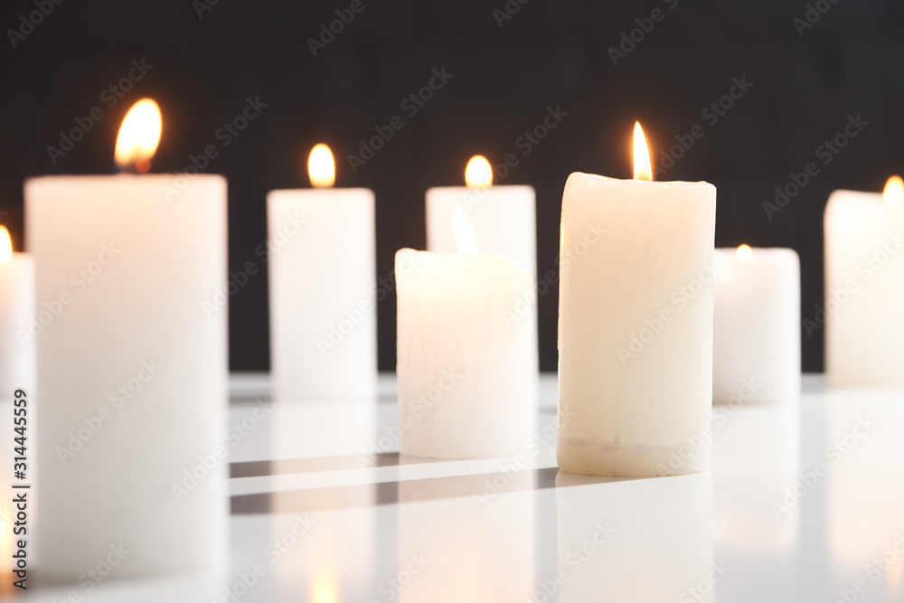 Fototapeta selective focus of burning white candles on white surface glowing isolated on black