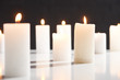 canvas print picture - selective focus of burning white candles on white surface glowing isolated on black