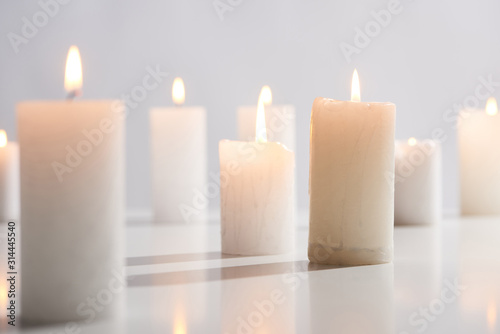 Fototapeta selective focus of burning white candles on white surface glowing isolated on gr