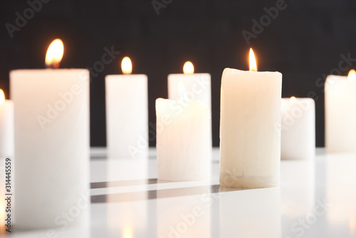 selective focus of burning white candles on white surface glowing isolated on black - 314445559