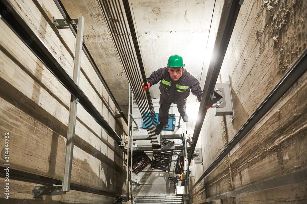 Fototapeta lift machinist repairing elevator in lift shaft