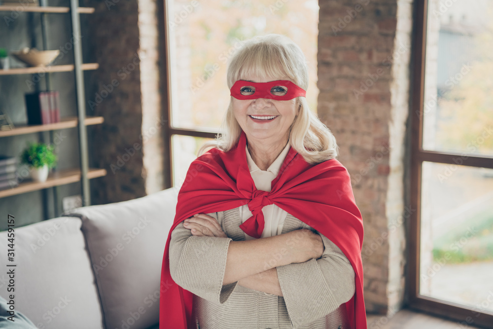 Fototapeta Close-up portrait of her she nice attractive cheerful cheery gray-haired lady wearing red costume super nanny planet save rescue service folded arm at industrial brick loft modern style interior house