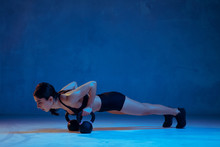 Caucasian Young Female Athlete Practicing On Blue Studio Background In Neon Light. Sportive Model Training Her Upper Body With Weights. Body Building, Healthy Lifestyle, Beauty And Action Concept.
