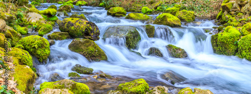 A small stream with a waterfall and mossy rocks in spring, panoramic image