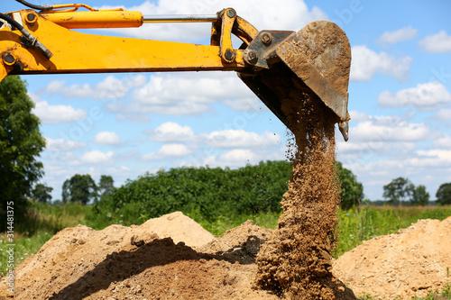 Fotografiet Yellow excavator shovel digging pit in ground