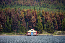Boathouse With Canoe On Pier In Autumn Pine Forest On Hill In Maligne Lake