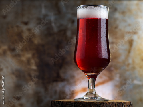 Photo A glass of red ale on a dark metal background