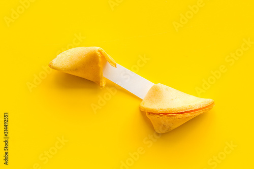 Fotografía Fortune cookie - broken piece with prediction inside - on yellow background copy