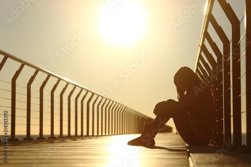 Fotografie, Obraz Sad teenager girl depressed sitting in a bridge at sunset