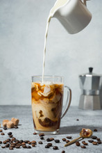 Iced Latte Coffee In Cup Glass With Pouring Milk