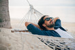 canvas print picture - A man enjoys calm, lies in a hammock on the background of the ocean and sunset.