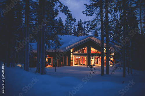 A cozy wooden cabin cottage chalet house covered in snow near ski resort in wint Fototapete