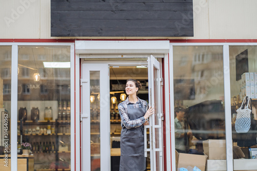 Photo  Beautiful asian woman store owner with standing in the doorway of her coffee shop looking at camera and smiling