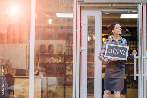 Beautiful asian woman store owner with standing in the doorway of her coffee shop looking at camera and smiling Tapéta, Fotótapéta