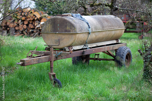 Agricultural old rusty trailer with a water tank on it Canvas Print