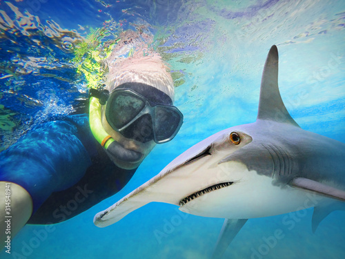Obraz Underwater selfie with friend. Scuba diver and shark on coral reef. Hammerhead shark - Sphyrna mokarran near Bahamas. Adventure in blue sea. - fototapety do salonu