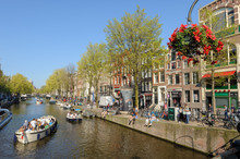 People In Canal Area Of Amsterdam During Spring Time
