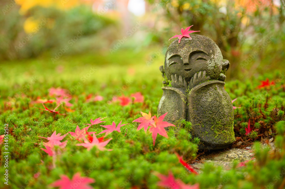 Red Maple leaf on head of Jizo sculpture doll (little Japanese Buddhist monk doll rock) in Japanese Garden.