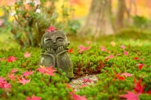 Red Maple Leaf On Head Of Jizo Sculpture Doll (little Japanese Buddhist Monk Doll Rock) In Japanese Garden.