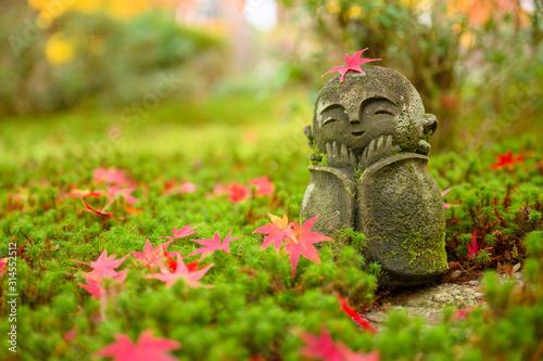 Obraz na plátne Red Maple leaf on head of Jizo sculpture doll (little Japanese Buddhist monk doll rock) in Japanese Garden