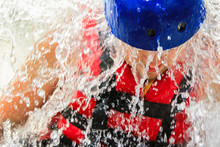 Close-up Strong Man In Red Life Jacket And Blue Helmet In Drops Of Water. Concept: Extreme Sports, Rafting, Outdoor Activities, People In Extreme Situations. Selective Focus.