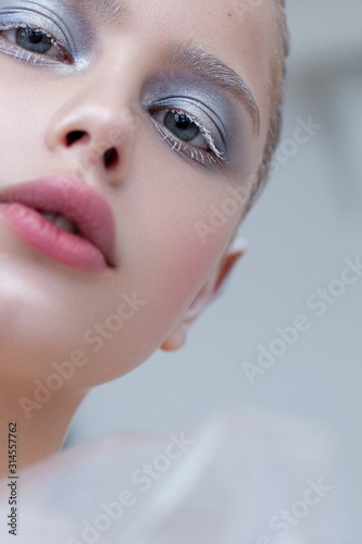 Fotografía  Artistic close up photo of a girl with blue eyes and winter make-up, snowy eyelashes and eyebrows