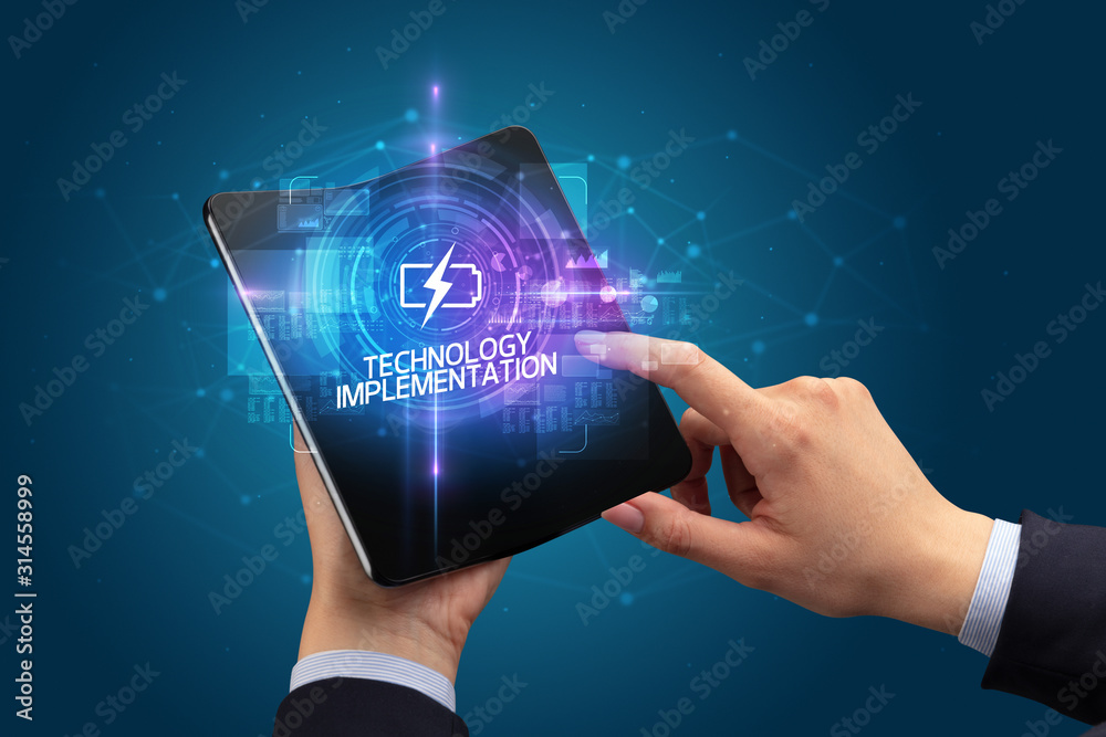 Fototapeta Businessman holding a foldable smartphone with MINING inscription, new technology concept TECHNOLOGY IMPLEMENTATION
