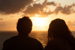 canvas print picture - A guy and a girl meet the sunset while sitting on a mountain. Silhouettes of a couple in love who are sitting with their backs to the camera and watching the bright sunset over the ocean. Romance,love