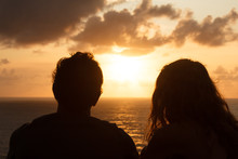 A Guy And A Girl Meet The Sunset While Sitting On A Mountain. Silhouettes Of A Couple In Love Who Are Sitting With Their Backs To The Camera And Watching The Bright Sunset Over The Ocean. Romance,love