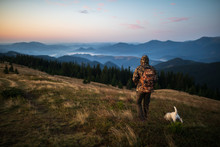 Hunter Man Dressed In Camouflage In The Mountains At Sunrise. Hunter With Dog In The Mountains