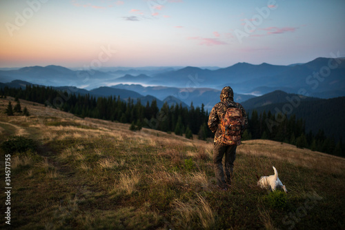 Canvas Print Hunter man dressed in camouflage in the mountains at sunrise
