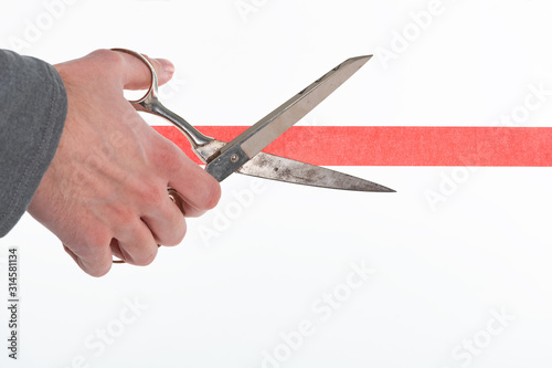 Fotomural Male hand cutting through red tape with scissors isolated on white with a shallo