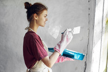 Young Woman Painting The Wall