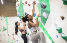 Friends Climbing An Indoor Wall In A Boudering Centre