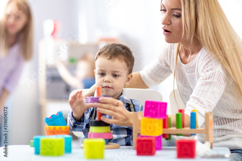 Fotografía mother and her son toddler building toy pyramid tower