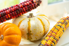 A Closeup View Of Several Halloween Decoration Pieces, Featuring Indian Corn And Small Pumpkins On A Window Sill.
