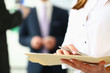 Focus on secretary with pretty manicure inspecting important business contract with concentration in modern office. Tender lady hands holding special pen. Company meeting concept. Blurred background