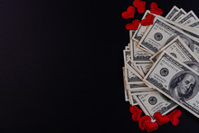 Dollar Bills On A Black Background And Red Hearts