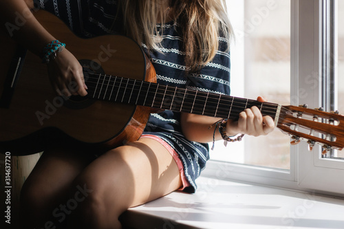 The young woman in the striped t-shirt sitting on the windowsill and playing acoustic guitar Fotobehang