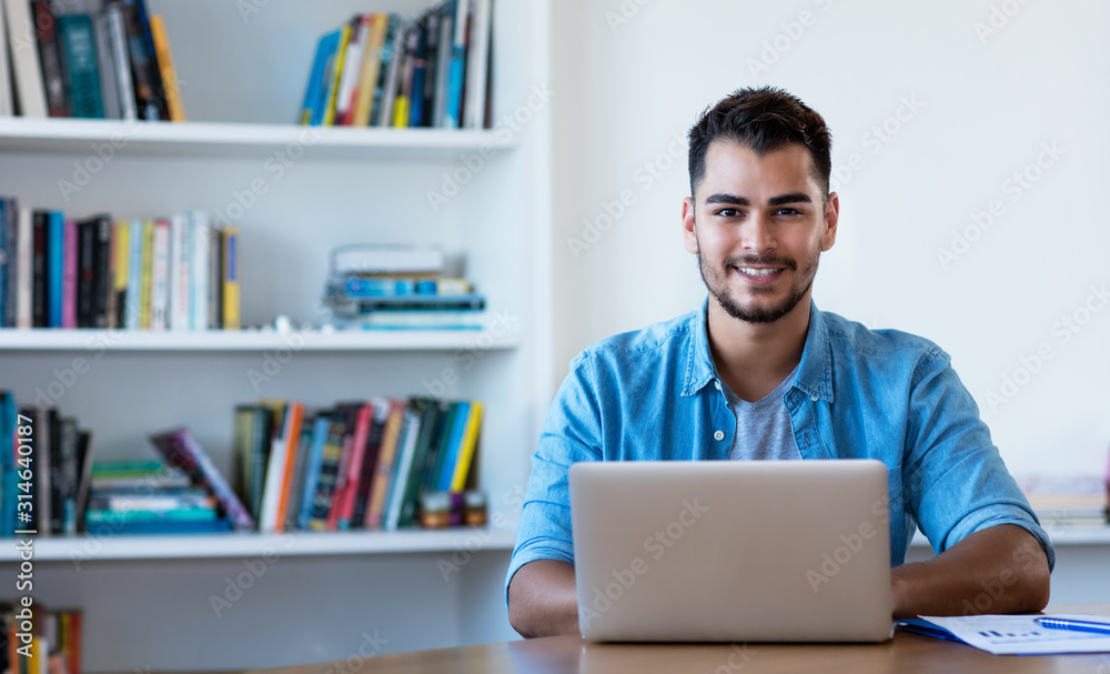 Fototapeta Handsome mexican hipster man working with computer