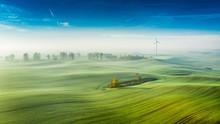 Foggy Green Field And Wind Turbine At Sunrise