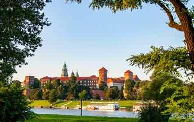 FototapetaKrakow, Poland. Historic royal Wawel castle, cathedral and Vistula River naturally framed with tress in fall in sunset light