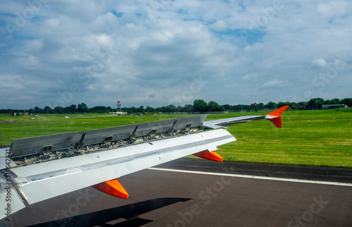 Photo Aircraft wing with extended flaps and spoilers while landing on the runway in th