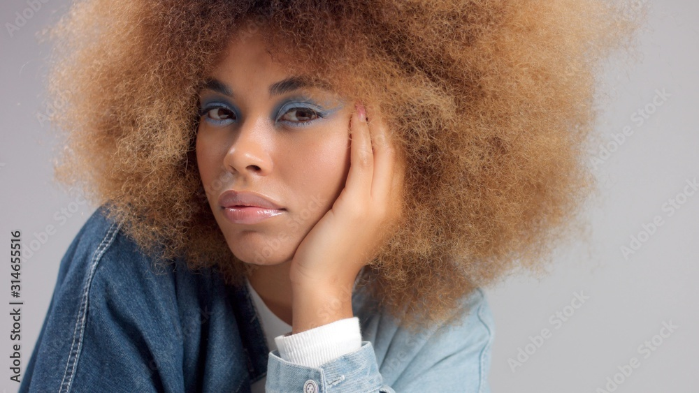 Fototapeta closeup of mixed race black woman in denim oversized shirt and huge afro hair watching to the camera with light blue eye makeup. Z generation