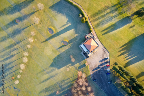 Obraz na plátně Aerial view of golf course green and clubhouse from above frozen grass in winter