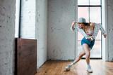 young woman touching cap and dancing hip-hop