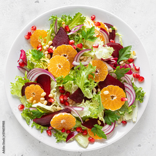 Fototapeta Christmas salad with boiled beet, red onion, tangerines, pomegranate, parsley, pine nuts and lettuce leaves obraz
